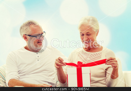 happy senior couple with gift box at home stock photo, family, holidays, christmas, age and people concept - happy senior couple with gift box over blue lights background by Syda Productions