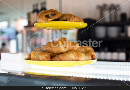 close up of croissants and buns on cake stand stock photo, food, baking, junk-food and unhealthy eating concept - close up of croissants and buns on cake stand at cafe or bakery by Syda Productions