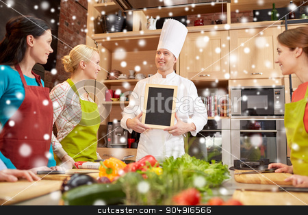 happy women and chef cook with menu in kitchen stock photo, cooking class, culinary, food and people concept - happy women and chef cook with blank menu chalk board in kitchen over snow effect by Syda Productions