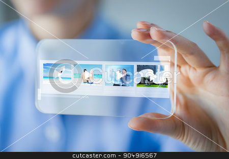 close up of woman with transparent smartphone stock photo, business, technology and people concept - close up of woman hand holding and showing transparent smartphone with media player icons on screen at office by Syda Productions
