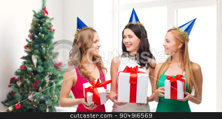 smiling women in party caps with gift boxes stock photo, presents, holidays, people and celebration concept - smiling women in party caps with gift boxes over living room and christmas tree background by Syda Productions