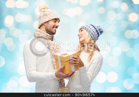 smiling couple in winter clothes with gift box stock photo, winter, holidays, couple, christmas and people concept - smiling man and woman in hats and scarf with gift box over blue holidays lights background by Syda Productions