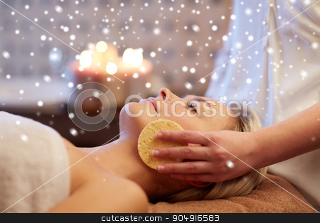 close up of woman having face massage in spa salon stock photo, people, beauty, spa, skin care and relaxation concept - close up of beautiful young woman lying with closed eyes and having face massage with sponge in spa with snow effect by Syda Productions