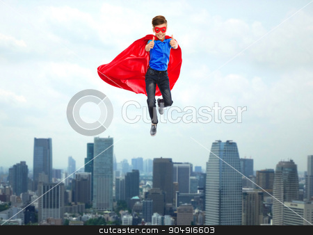 boy in super hero cape and mask showing thumbs up stock photo, gesture, freedom, childhood, movement and people concept - boy in red super hero cape and mask flying in air and showing thumbs up over city background by Syda Productions