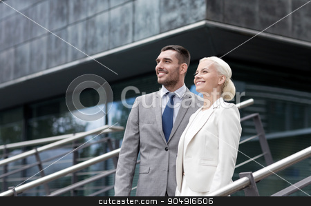 smiling businessmen standing over office building stock photo, business, partnership, success and people concept - smiling businessman and businesswoman standing over office building by Syda Productions