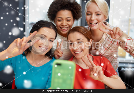 happy young women taking selfie with smartphone stock photo, people, leisure, friendship, gesture and technology concept - happy young women taking selfie with smartphone and showing victory gesture over snow effect by Syda Productions