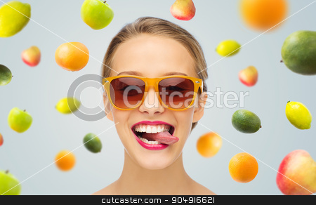 happy young woman in sunglasses showing tongue stock photo, people, expression, joy and fashion concept - smiling young woman in sunglasses with pink lipstick on lips showing tongue by Syda Productions