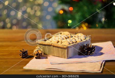 close up of christmas oat cookies on wooden table stock photo, christmas, holidays, food and baking concept - close up of oat cookies in wooden box and cinnamon on table over lights by Syda Productions