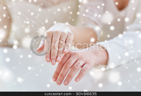 close up of lesbian couple hands and wedding rings stock photo, people, homosexuality, same-sex marriage and love concept - close up of happy lesbian couple hands showing wedding rings on over snow effect by Syda Productions