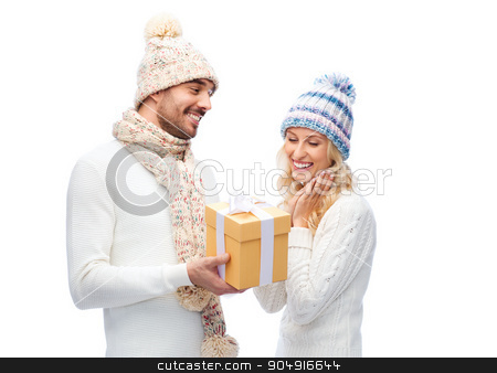 smiling couple in winter clothes with gift box stock photo, winter, holidays, couple, christmas and people concept - smiling man and woman in hats and scarf with gift box by Syda Productions
