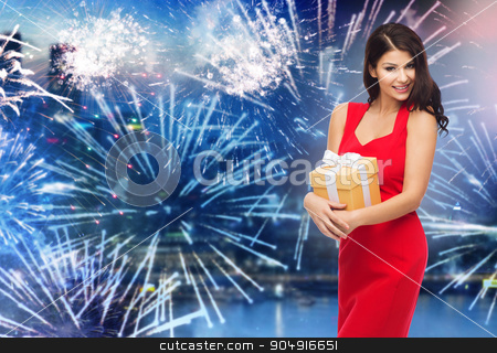 happy woman in red dress with gift over firework stock photo, people, holidays, christmas, new year party and celebration concept - beautiful sexy woman in red dress with gift box over night city and firework background by Syda Productions