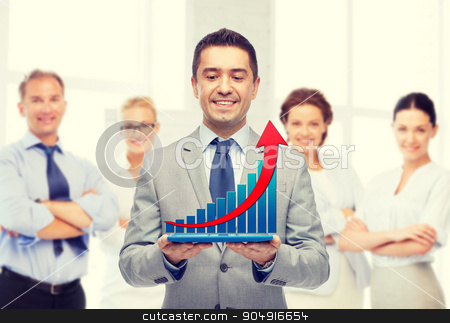 happy businessman in suit holding tablet pc stock photo, business, people, success and technology concept - happy smiling businessman in suit holding tablet pc computer with virtual graph over group of people and office room background by Syda Productions