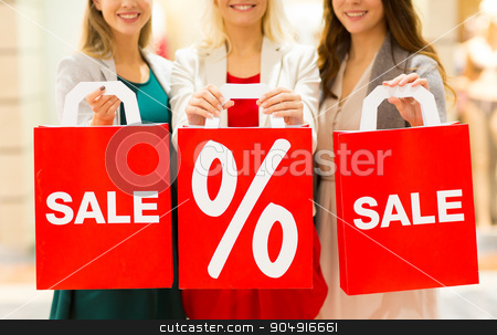 close up of happy women with shopping bags in mall stock photo, consumerism and people concept - close up of happy young women holding shopping bags with sale and percentage sign in mall by Syda Productions