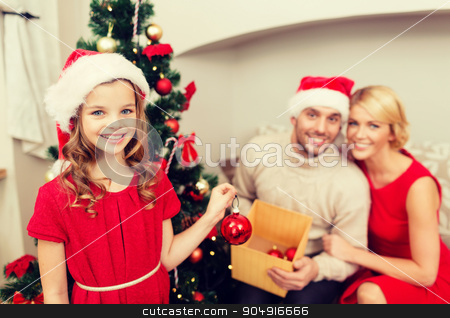 smiling family decorating christmas tree stock photo, family, christmas, x-mas, happiness and people concept - smiling family in santa helper hats decorating christmas tree by Syda Productions