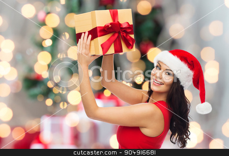happy woman in santa hat with gift over lights stock photo, people, holidays, christmas and celebration concept - beautiful sexy woman in red dress and santa hat with gift box over holidays lights background by Syda Productions