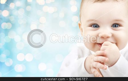 happy baby face over blue holidays lights stock photo, babyhood, childhood and people concept - happy baby face over blue holidays lights background by Syda Productions