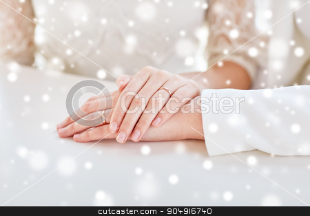 close up of lesbian couple hands with rings stock photo, people, homosexuality, same-sex marriage and love concept - close up of lesbian couple hands with wedding rings over snow effect by Syda Productions