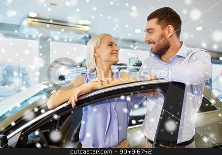 happy couple buying car in auto show or salon stock photo, auto business, car sale, consumerism and people concept - happy couple buying car in auto show or salon over snow effect by Syda Productions