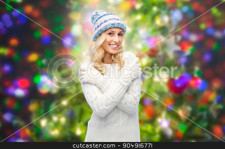smiling young woman in winter hat and sweater stock photo, winter, fashion, christmas and people concept - smiling young woman in winter hat, sweater and gloves over holidays lights background by Syda Productions
