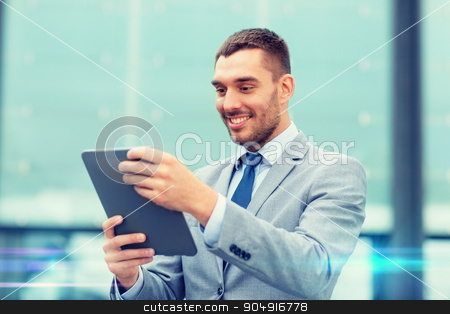 smiling businessman with tablet pc outdoors stock photo, business, education, technology and people concept - smiling businessman working with tablet pc computer on city street by Syda Productions