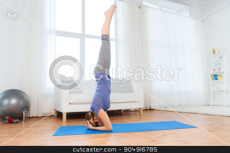 woman making yoga in headstand pose on mat stock photo, fitness, sport, people and healthy lifestyle concept - woman making yoga in headstand pose on mat by Syda Productions
