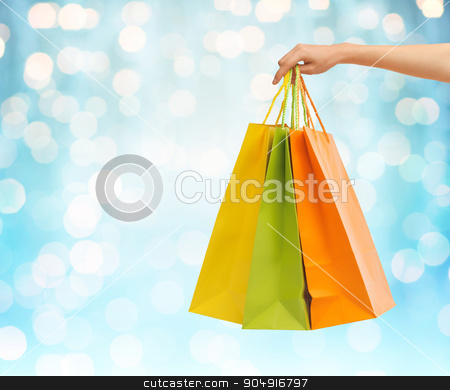close up of hand holding shopping bags stock photo, people, sale, consumerism and advertisement concept - close up of hand holding shopping bags over blue holidays lights background by Syda Productions