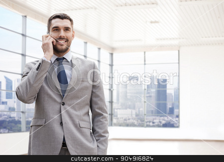happy young businessman calling on smartphone stock photo, business, people and office concept - happy young businessman calling on smartphone over office room or new apartment background by Syda Productions