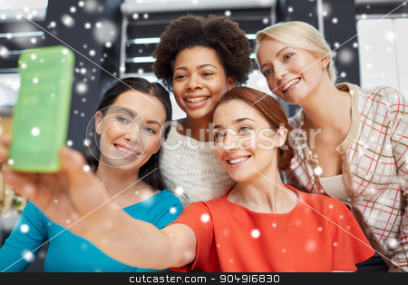 happy young women taking selfie with smartphone stock photo, people, leisure, friendship and technology concept - happy young women taking selfie with smartphone over snow effect by Syda Productions