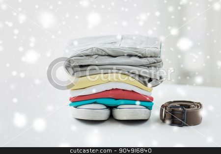 close up of clothes and accessories on table stock photo, clothes, personal staff and objects concept - close up of folded shirts, pants, belt and shoes on table at home over snow effect by Syda Productions