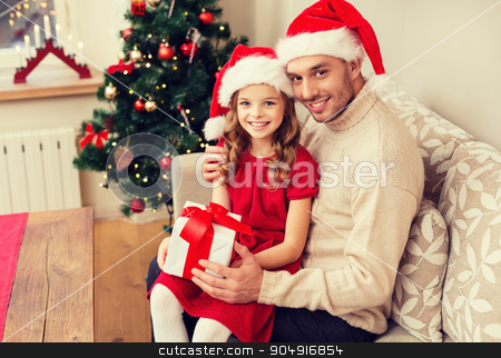 smiling father and daughter holding gift box stock photo, christmas, x-mas, winter, happiness and people concept - smiling father and daughter in santa helper hats holding gift box by Syda Productions