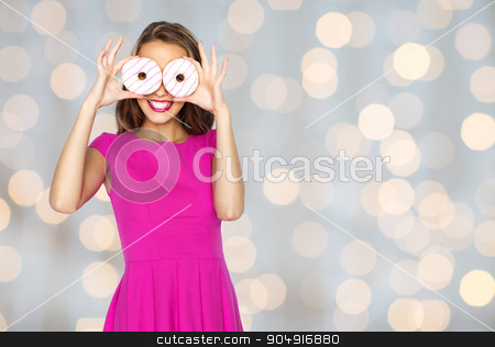 happy woman or teen girl looking through donuts stock photo, people, holidays, junk food and fast food concept - happy young woman or teen girl in pink dress having fun and looking through donuts over lights background by Syda Productions
