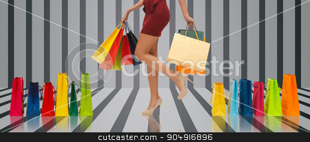 close up of woman on high heels with shopping bags stock photo, people, sale and consumerism concept - close up of woman in red short skirt and high heeled shoes with shopping bags over gray striped 3d background by Syda Productions