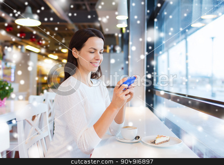 smiling woman with smartphone and coffee at cafe stock photo, drinks, food, people, technology and lifestyle concept - smiling young woman with smartphone drinking coffee at cafe over snow effect by Syda Productions