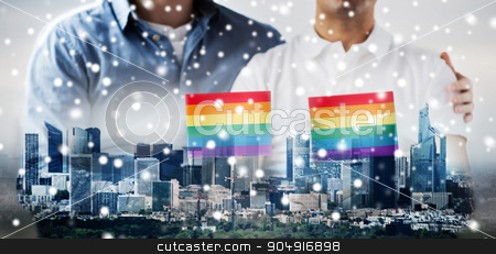 close up of male gay couple holding rainbow flags stock photo, people, homosexuality, same-sex marriage, gay and love concept - close up of happy male gay couple hugging and holding rainbow flags over city background and snow effect by Syda Productions