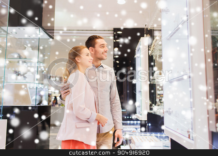 couple looking to shopping window at jewelry store stock photo, sale, consumerism and people concept - happy couple looking at shopping window in jewelry store in mall with snow effect by Syda Productions