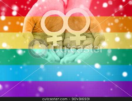 close up of lesbian couple hands with venus symbol stock photo, people, homosexuality, same-sex marriage, gay pride and love concept - close up of happy lesbian couple hands holding white paper venus symbol over rainbow flag stripes background over snow effect by Syda Productions