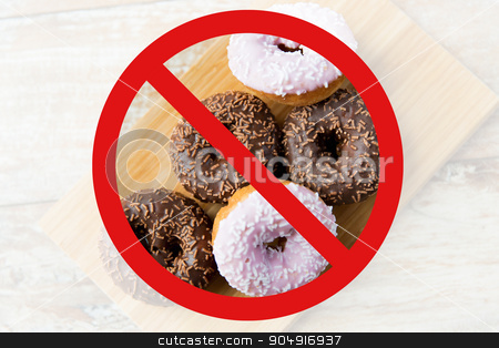 close up of glazed donuts pile behind no symbol stock photo, fast food, low carb diet, fattening and unhealthy eating concept - close up of glazed donuts on wooden board behind no symbol or circle-backslash prohibition sign by Syda Productions