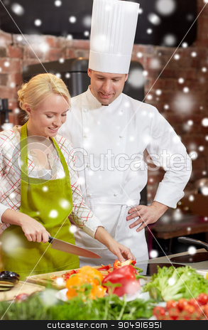happy male chef cook with woman cooking in kitchen stock photo, cooking class, culinary, food and people concept - happy male chef cook with woman cooking in kitchen over snow effect by Syda Productions