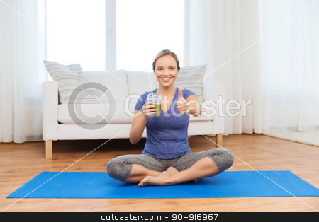 woman with smoothie showing thumbs up at home stock photo, fitness, sport, people, diet and healthy lifestyle concept - happy woman with cup of smoothie sitting on mat at home and showing thumbs up by Syda Productions
