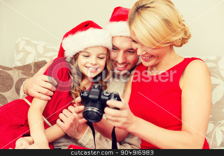 family in santa helper hats looking at pictires stock photo, family, christmas, x-mas, happiness and people concept - smiling family in santa helper hats looking at pictures by Syda Productions