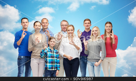 group of smiling people showing ok hand sign stock photo, gesture, family, generation and people concept - group of smiling men, women and boy showing ok hand sign over blue sky and clouds background by Syda Productions
