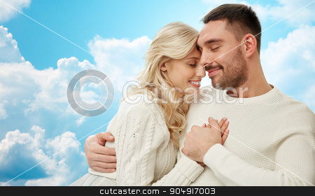 happy couple cuddling over blue sky and clouds stock photo, family, love, happiness, affection and people concept - happy couple cuddling over blue sky and clouds background by Syda Productions