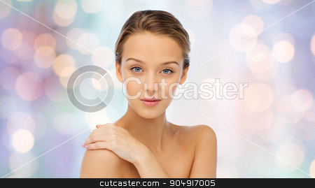 smiling young woman face and shoulders stock photo, beauty, people, body care and health concept - smiling young woman face and hand on bare shoulder over purple holidays lights background by Syda Productions