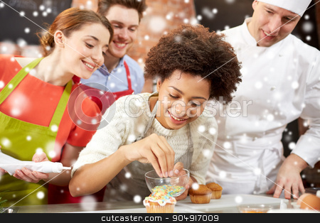 happy friends and chef cook baking in kitchen stock photo, cooking class, culinary, bakery, food and people concept - happy group of friends and male chef cook baking in kitchen over snow effect by Syda Productions