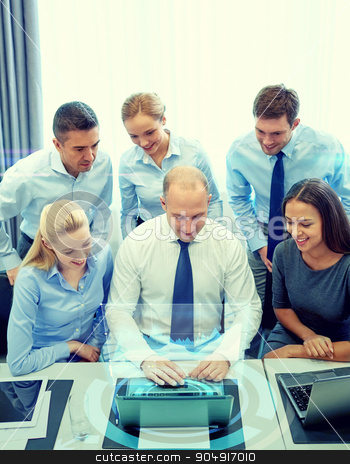 smiling business people with laptop in office stock photo, business, people, technology and teamwork concept - smiling business team with laptop computer and virtual projection working in office by Syda Productions