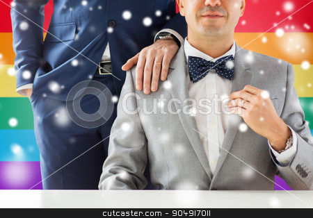 close up of male gay couple with wedding rings on stock photo, people, celebration, homosexuality, same-sex marriage and love concept - close up of male gay couple with wedding rings on putting hand on shoulder over rainbow flag background and snow effect by Syda Productions