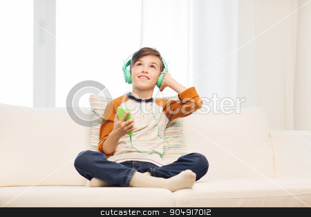 happy boy with smartphone and headphones at home stock photo, leisure, children, technology and people concept - smiling boy with smartphone and headphones listening to music at home by Syda Productions
