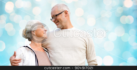 happy senior couple over blue holidays lights stock photo, family, old age, love and people concept - happy senior couple over blue holidays lights background by Syda Productions