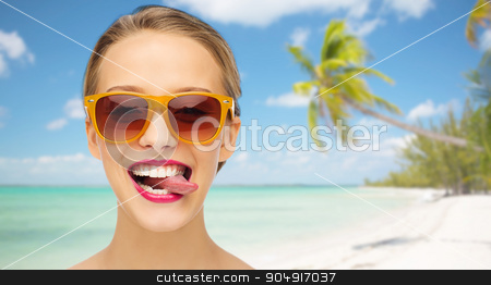 happy young woman in sunglasses showing tongue stock photo, people, expression, summer vacation, travel and fashion concept - smiling young woman in sunglasses with pink lipstick on lips showing tongue over tropical beach with palm background by Syda Productions