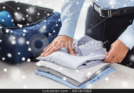 businessman packing clothes into travel bag stock photo, business, trip, luggage and people concept - happy businessman packing clothes into travel bag over snow effect by Syda Productions